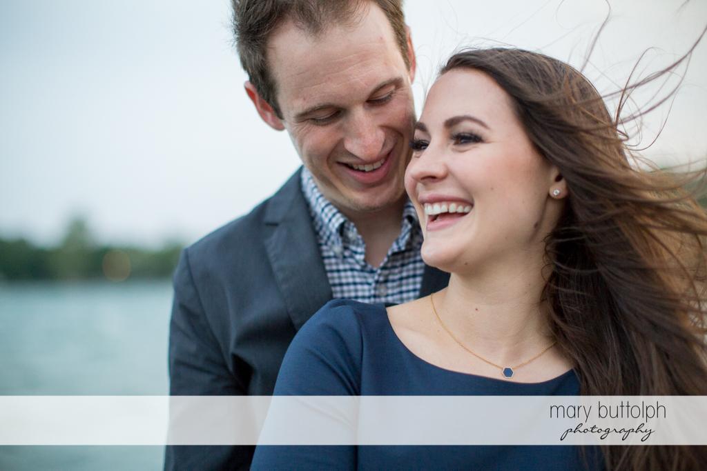 Couple enjoy the view at the lake at Skaneateles Lake Engagement