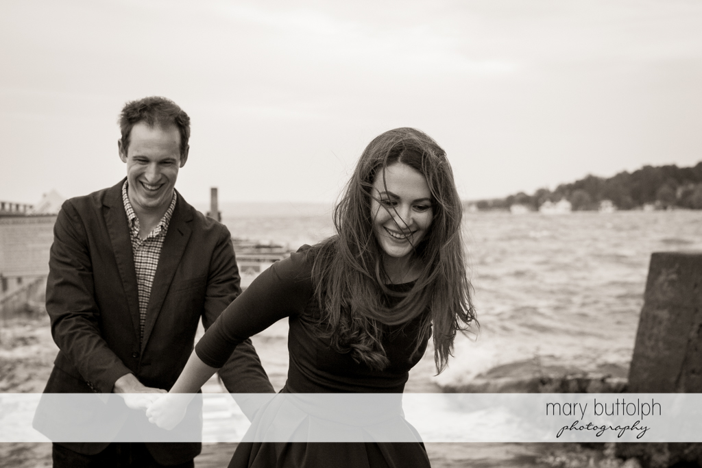 Couple hold hands by the lake at Skaneateles Lake Engagement