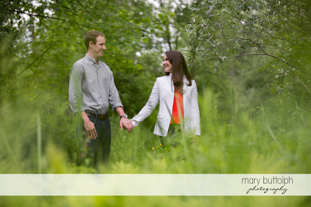 Couple hold hands as they stroll in the park at Skaneateles Lake Engagement