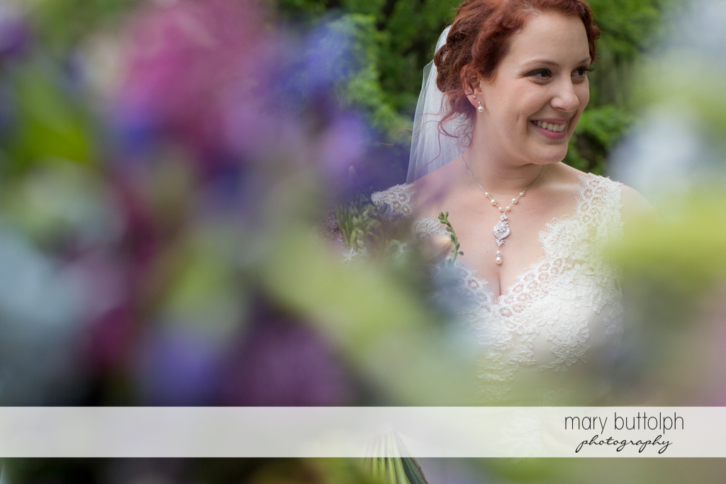 Bride as seen through the plants in the garden at Frog Pond Bed & Breakfast Wedding