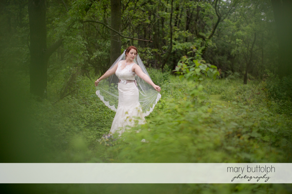 Bride shows her wedding dress in the woods at Frog Pond Bed & Breakfast Wedding