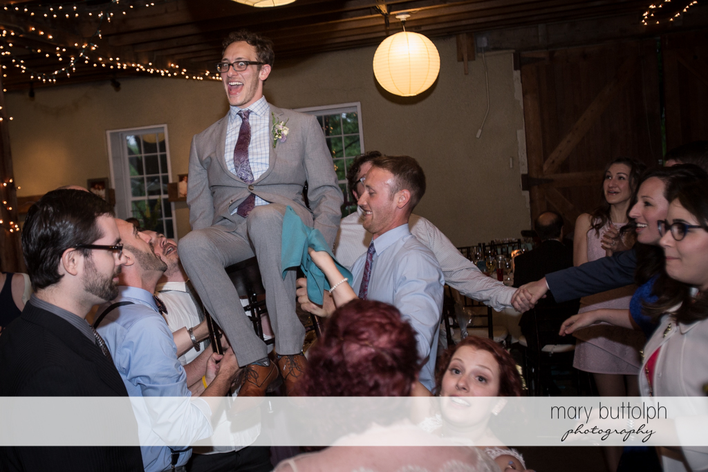 Groom is carried by groomsmen at Frog Pond Bed & Breakfast Wedding