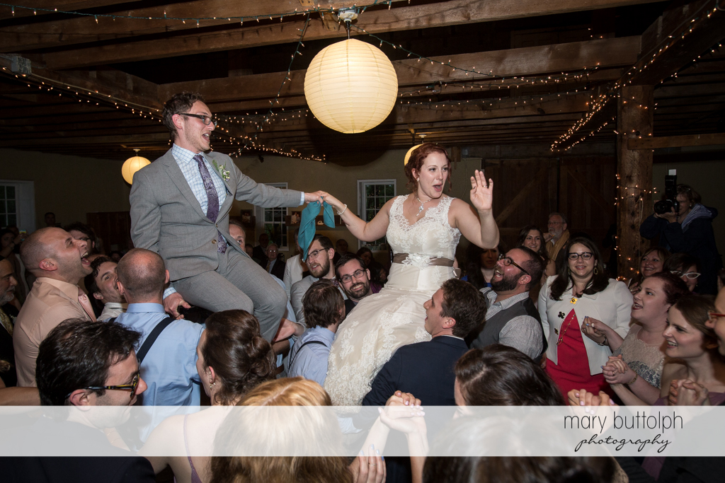 Couple stand out in the crowd as they are carried by guests at Frog Pond Bed & Breakfast Wedding