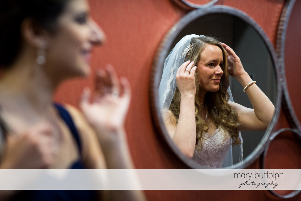 Brides adjusts her wedding veil at the Lodge at Welch Allyn Wedding