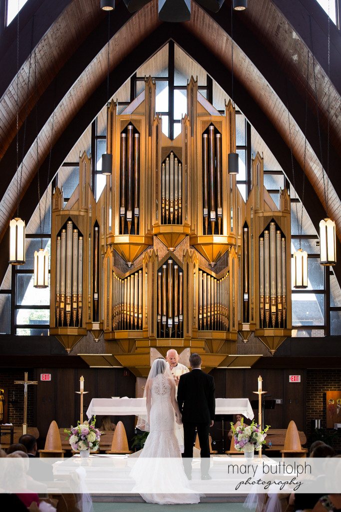 Couple listen to the priest at the Lodge at Welch Allyn Wedding