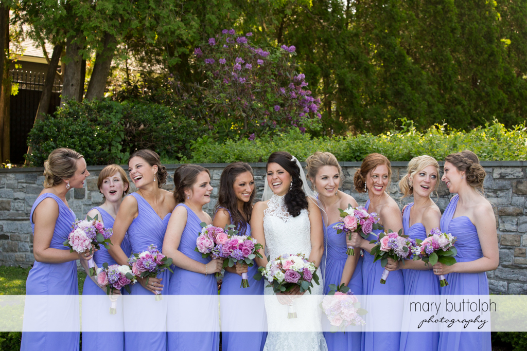 Bride and bridesmaids with bouquets in a candid shot in front of a brick wall at the Lodge at Welch Allyn Wedding