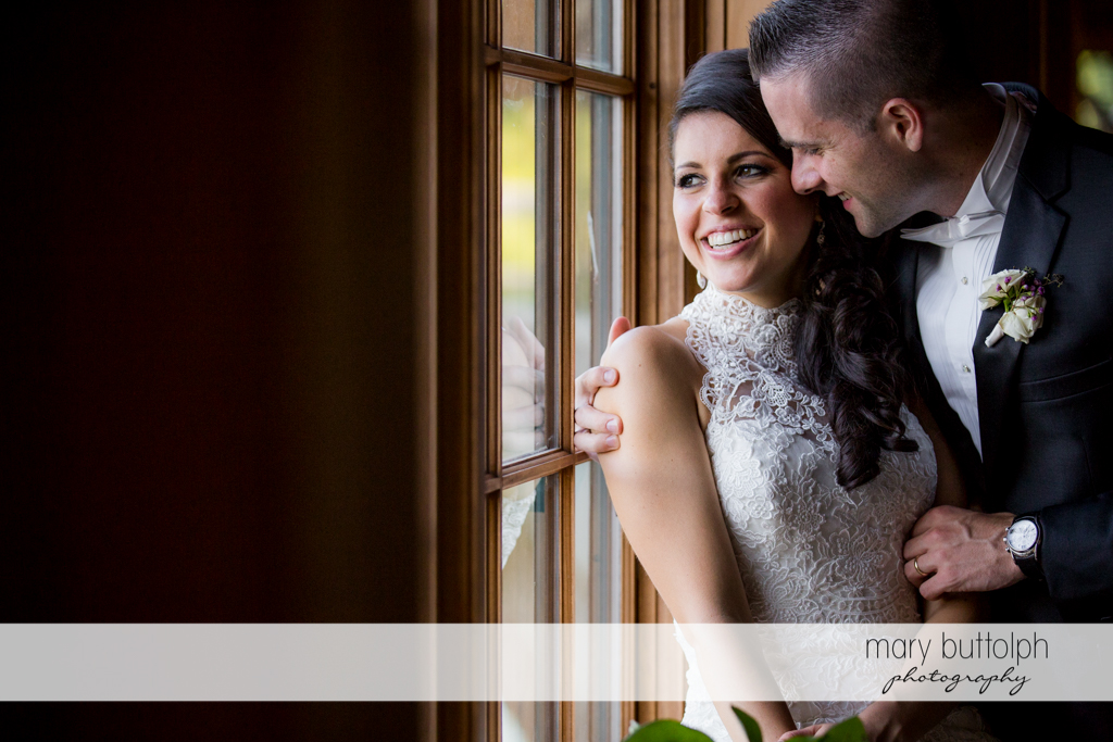 Couple pose by the window at the Lodge at Welch Allyn Wedding