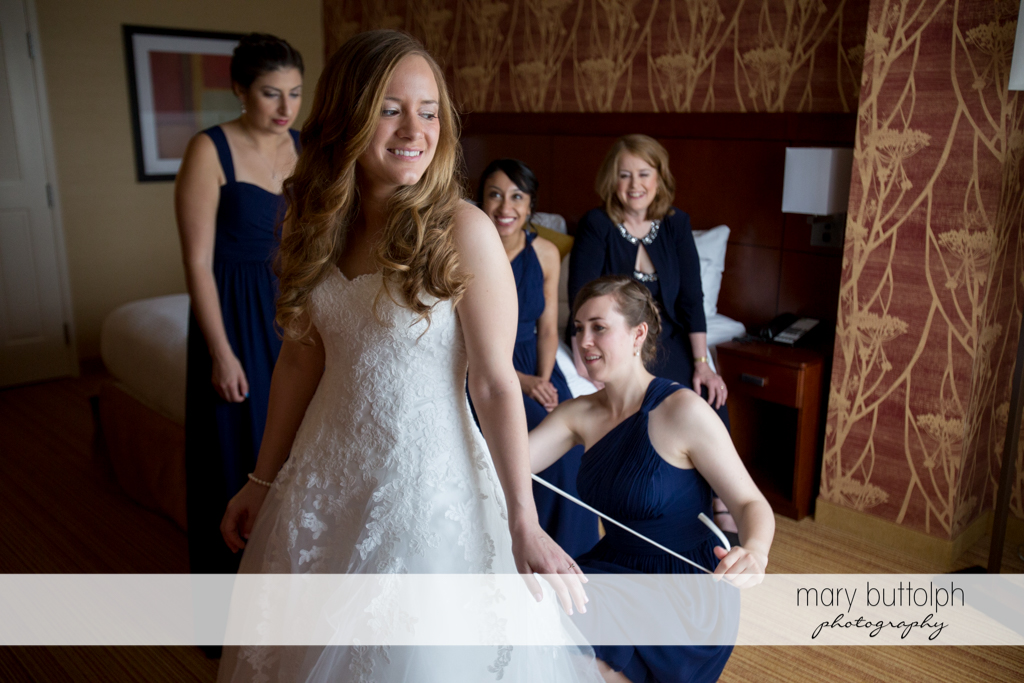 Bridesmaids help bride slip on her wedding dress at the Lodge at Welch Allyn Wedding