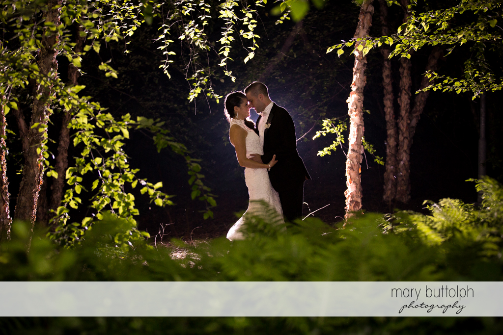 Couple rub noses in the moonlight in the garden at the Lodge at Welch Allyn Wedding