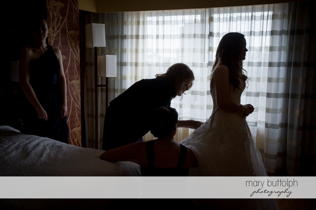 Bridesmaid fixes the bride's wedding gown at the Lodge at Welch Allyn Wedding