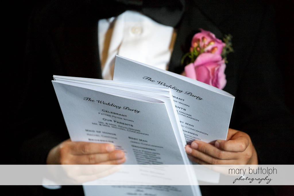 Man holds copies of the wedding program at the Lodge at Welch Allyn Wedding