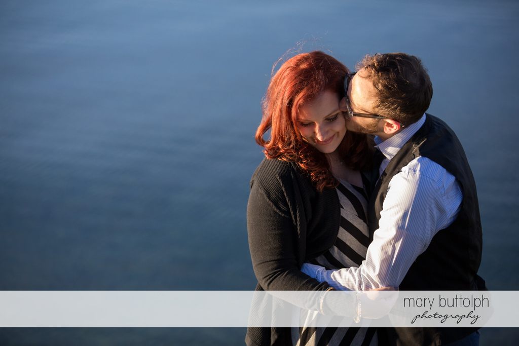 Couple kiss by the lake at Skaneateles Engagement