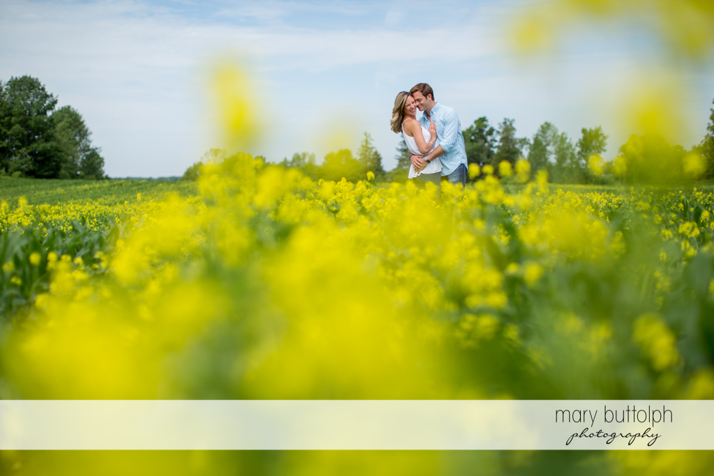 Couple hug in the garden full of flowers at Skaneateles Engagement