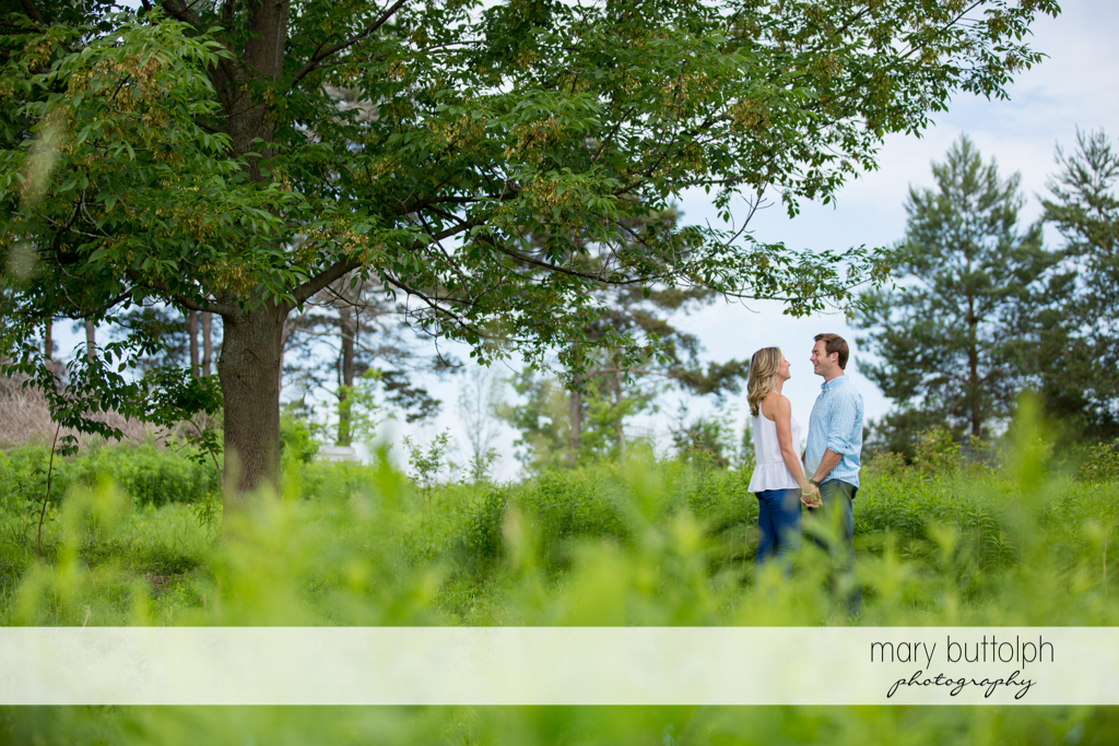 Couple hold hands in the middle of the park at Skaneateles Engagement