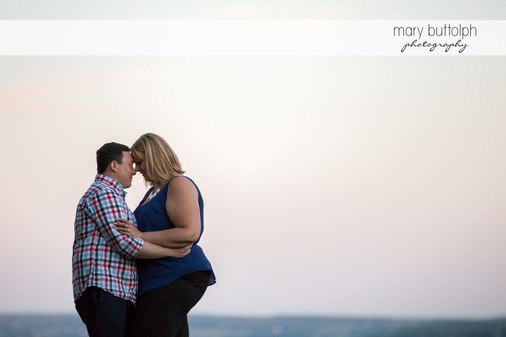 Couple hug by the lakeside at Skaneateles Lake Engagement