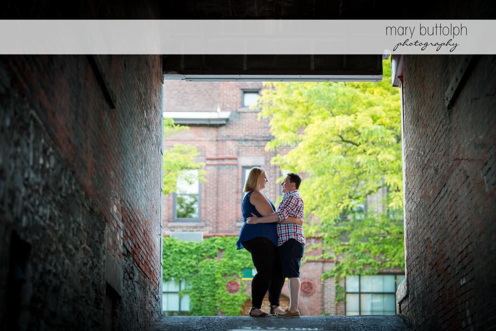 Couple stand between brick walls at Skaneateles Lake Engagement