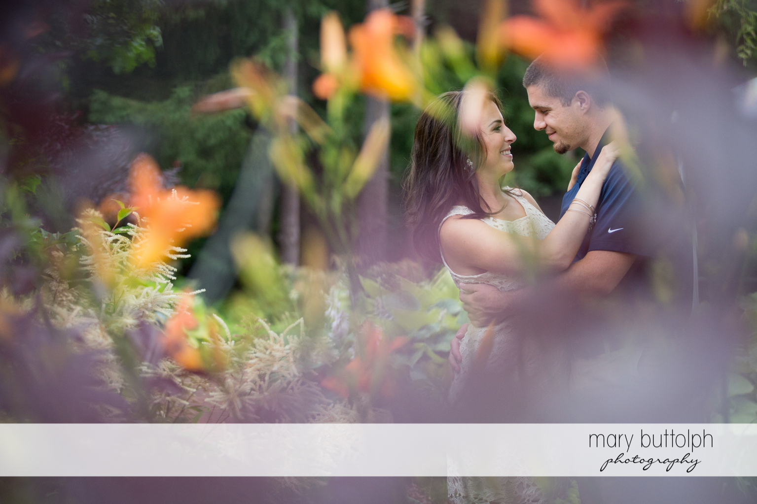 Couple pose by the flowers at Skaneateles Engagement