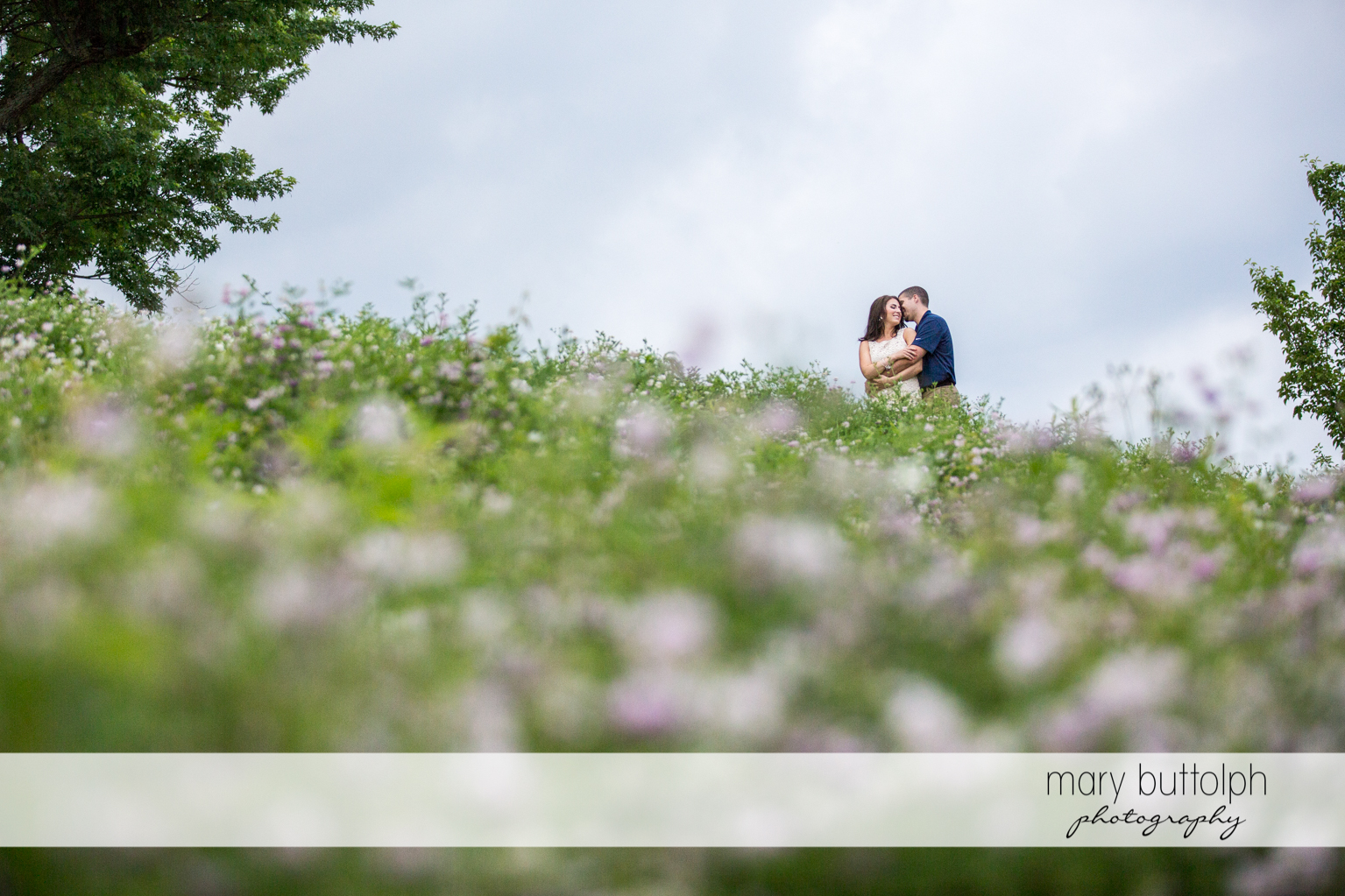 Couple embrace in the garden full of flowers at Skaneateles Engagement