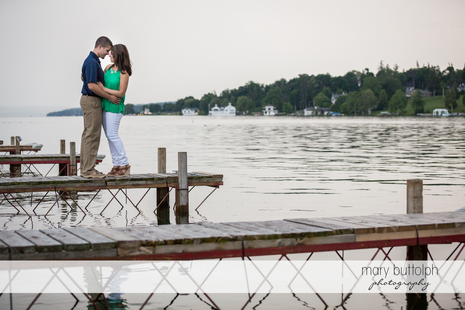 Couple hug by the lake at Skaneateles Engagement