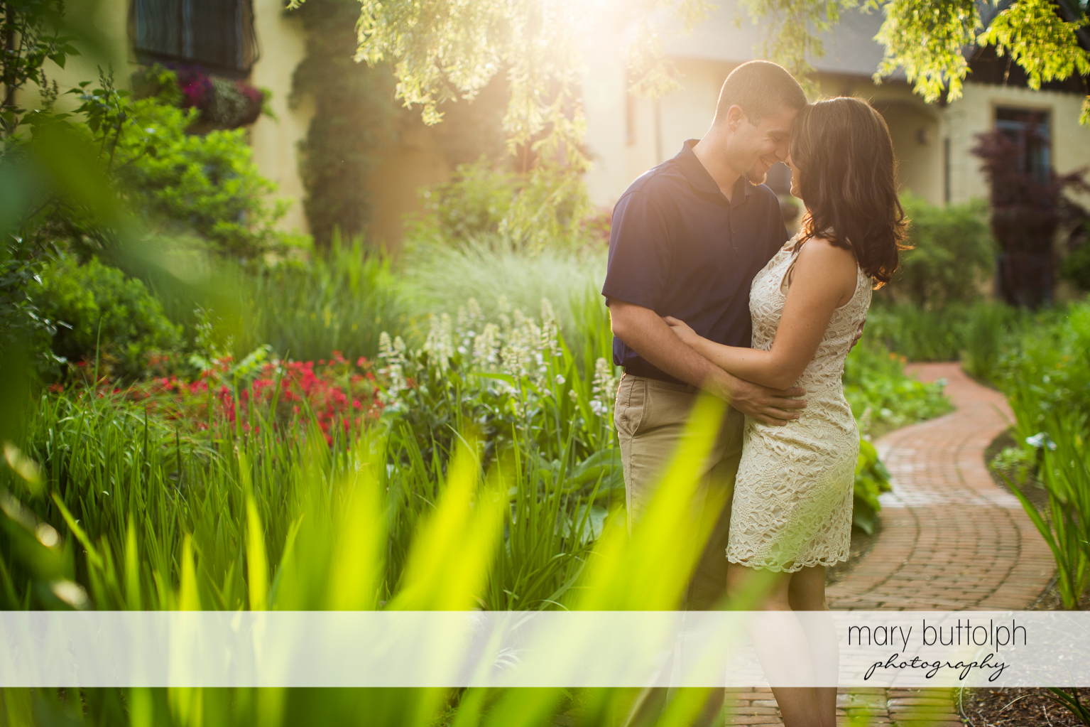 Couple cuddle up in the garden in front of a house at Skaneateles Engagement