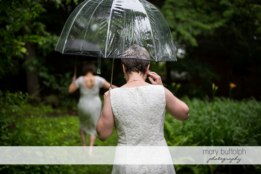 Same sex couple carrying umbrellas stroll in the woods at Mandana Barn Wedding
