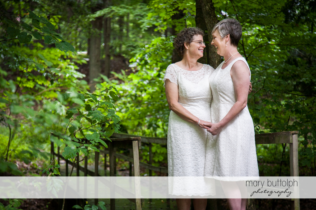 Same sex couple hold hands on a wooden bridge in the woods at Mandana Barn Wedding
