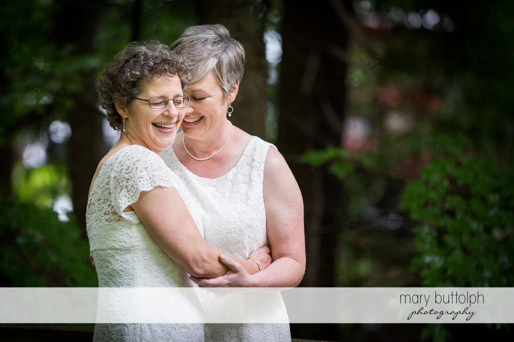Same sex couple share a happy moment in the woods at Mandana Barn Wedding