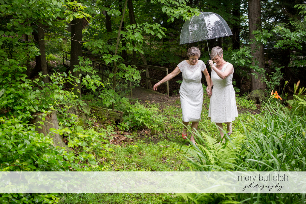 Same sex couple take a walk in the woods at Mandana Barn Wedding