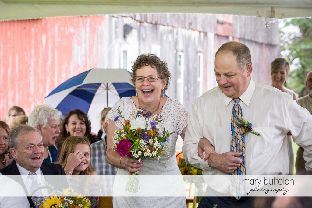Bride and a relative walk down the aisle at Mandana Barn Wedding