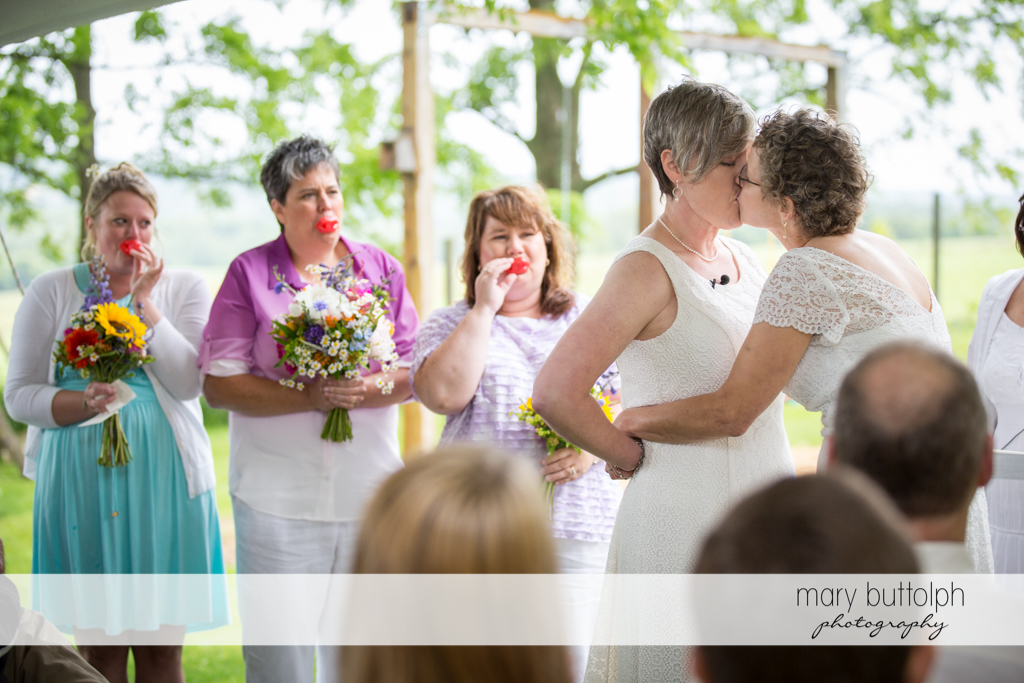 Couple kiss as guests blow lip whistles at Mandana Barn Wedding