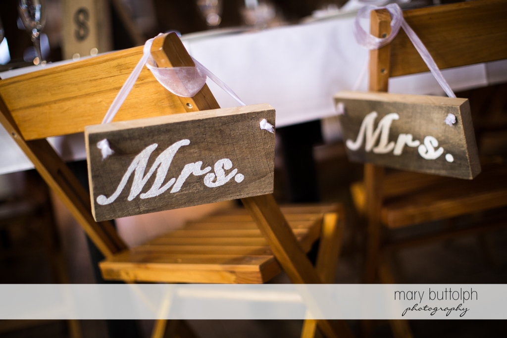 Signs showing the same sex couple's seats at Mandana Barn Wedding