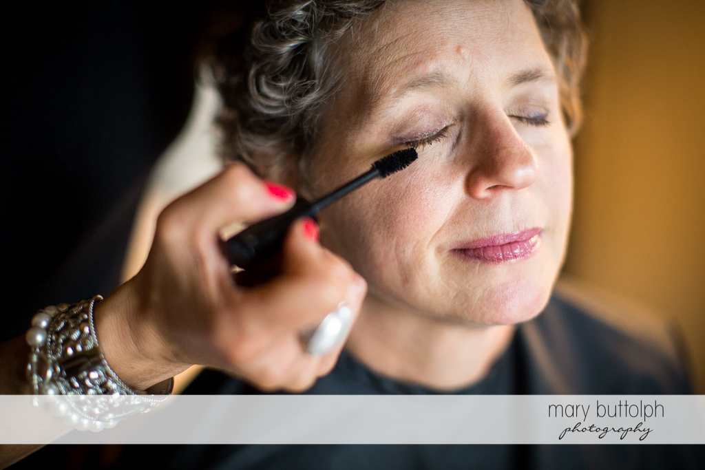 Makeup artist applies mascara to the bride's eyelashes at Mandana Barn Wedding