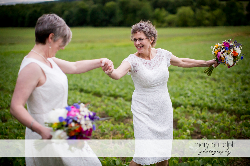 Same sex couple dance in the field at Mandana Barn Wedding