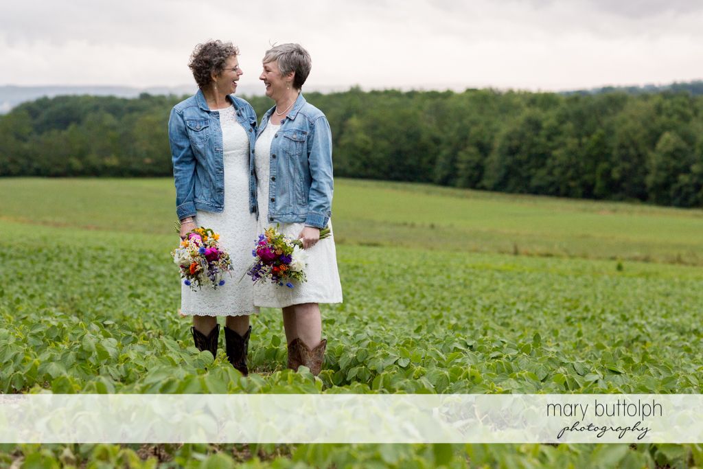 Same sex couple with matching boots and jackets at Mandana Barn Wedding