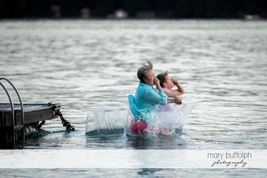 Same sex couple dive in the lake at Mandana Barn Wedding