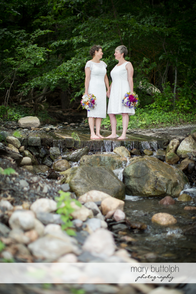 Same sex couple with bouquets pose by the lake at Mandana Barn Wedding