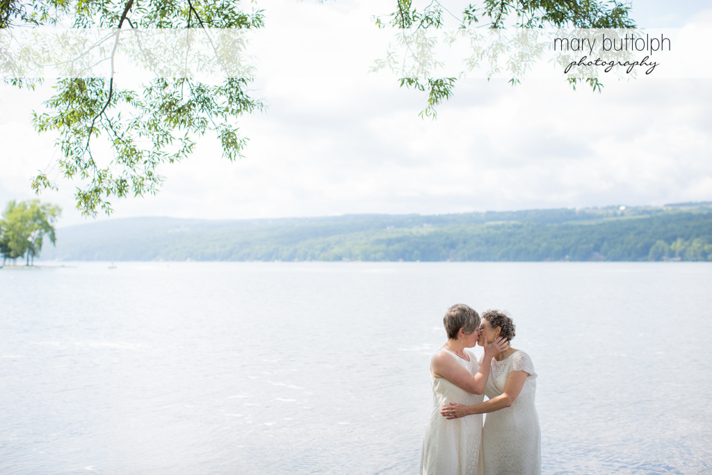 Same sex couple kiss in the lake at Mandana Barn Wedding