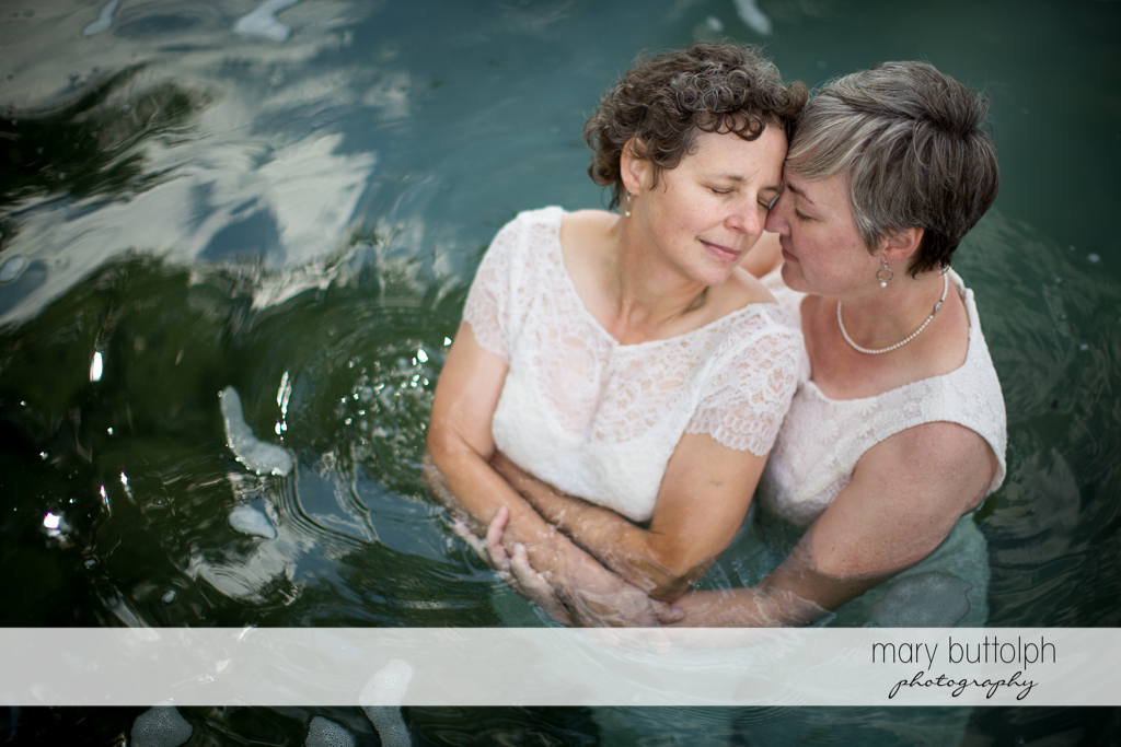 Same sex couple share a tender moment in the lake at Mandana Barn Wedding