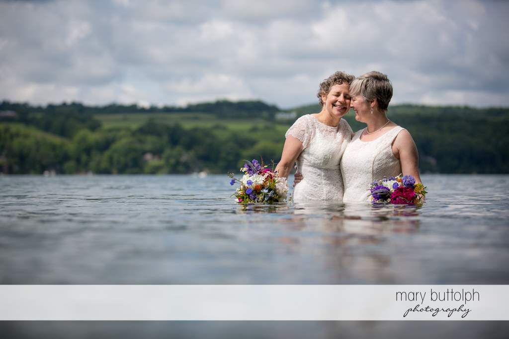 Same sex couple celebrate their union in the lake at Mandana Barn Wedding