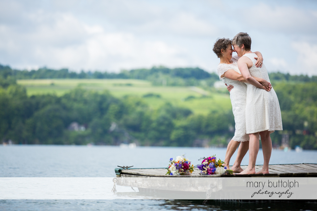 Same sex couple rub noses near the lake at Mandana Barn Wedding