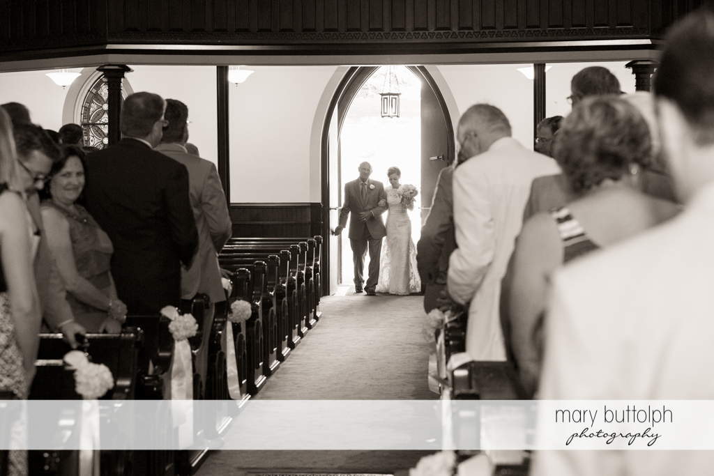 Bride and her father walk down the aisle as guests look on at the Inns of Aurora Wedding