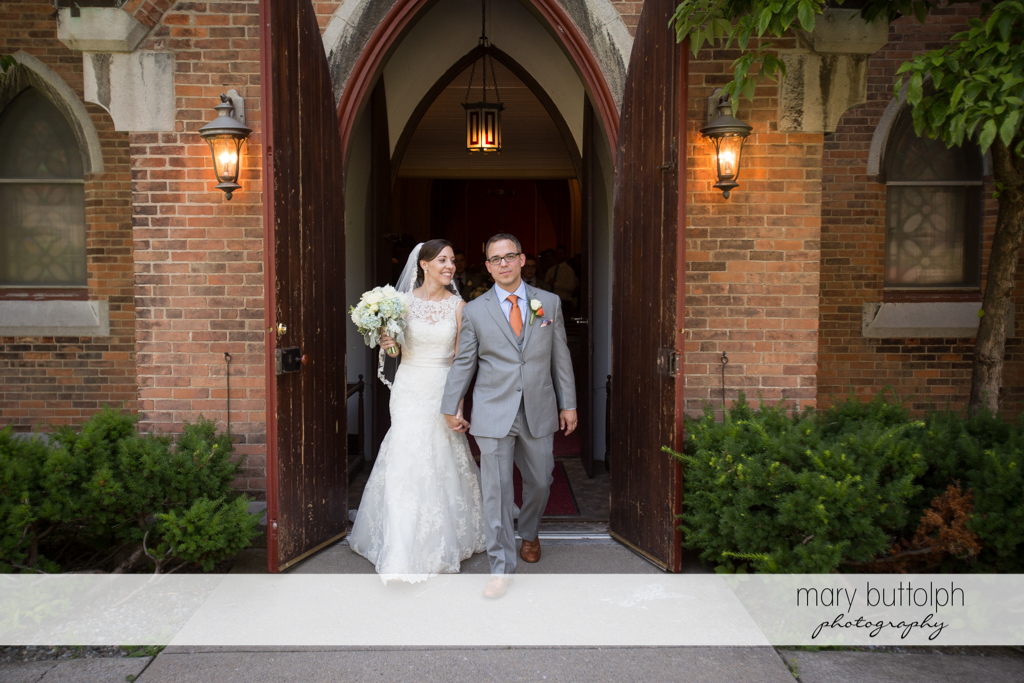 Couple leave church at the Inns of Aurora Wedding