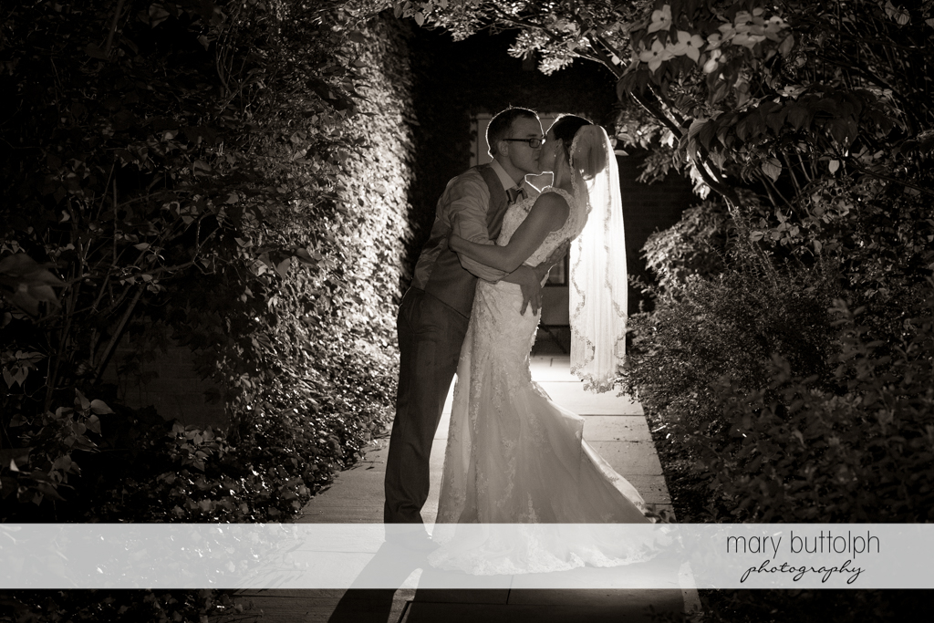 Couple kiss in the moonlight at the Inns of Aurora Wedding