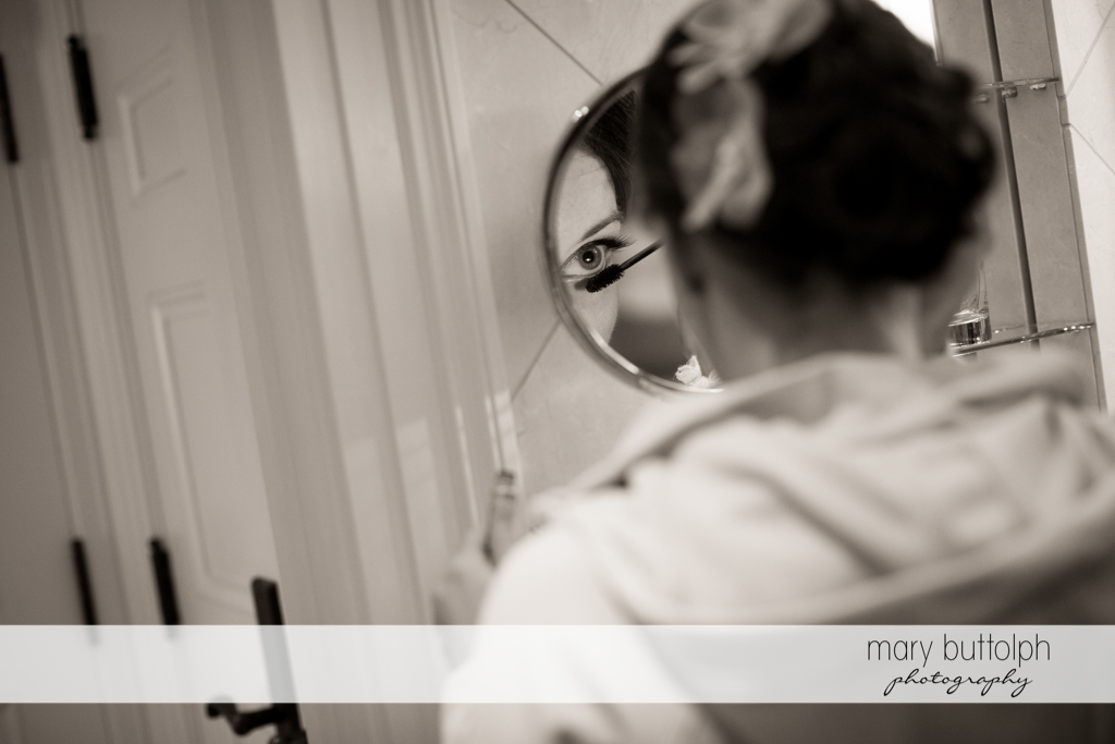 Bride applies mascara to her eyelashes at the Inns of Aurora Wedding