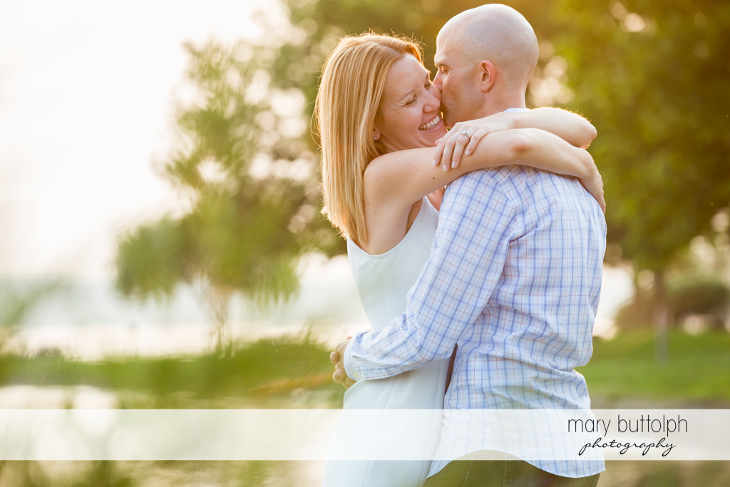 Couple embrace in the park at Aurora Engagement