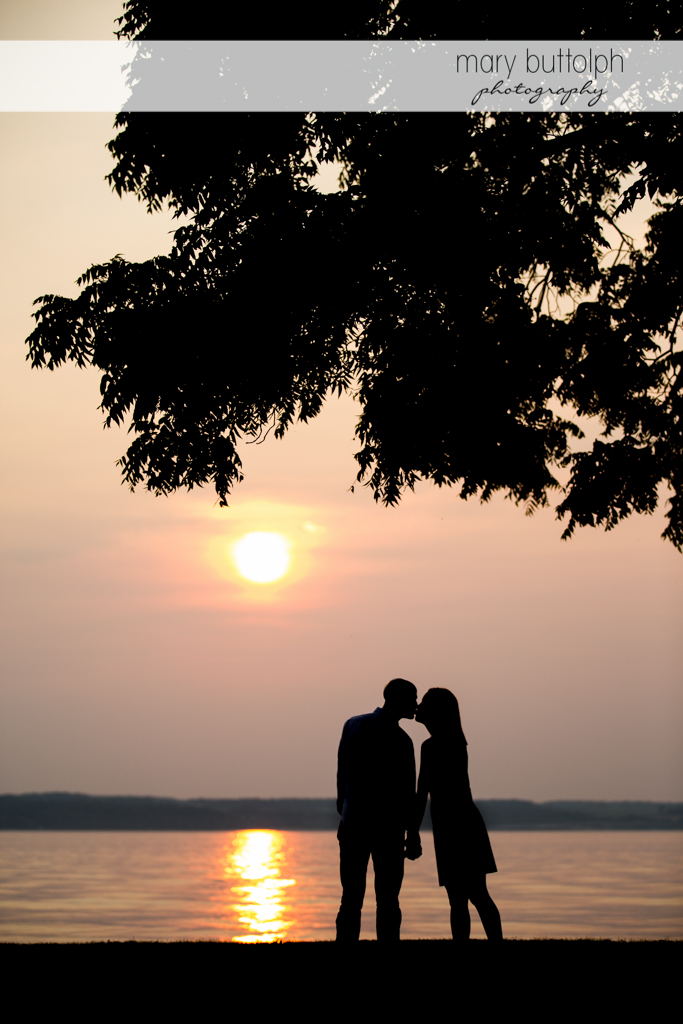 Couple kiss by the lake as the sun sets at Aurora Engagement