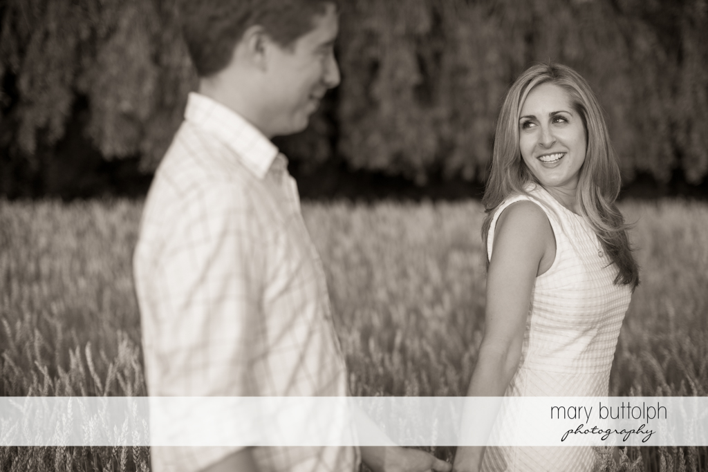 Couple traverse the wheat field at Skaneateles Engagement