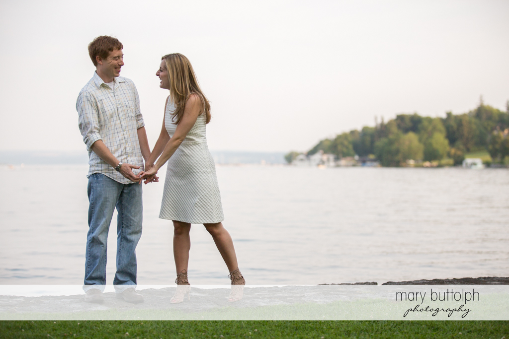Couple stand by the lake at Skaneateles Engagement
