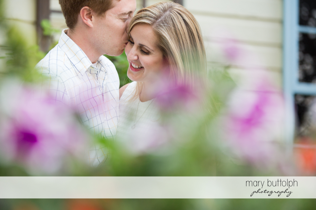 Couple pose in front of flowers at Skaneateles Engagement