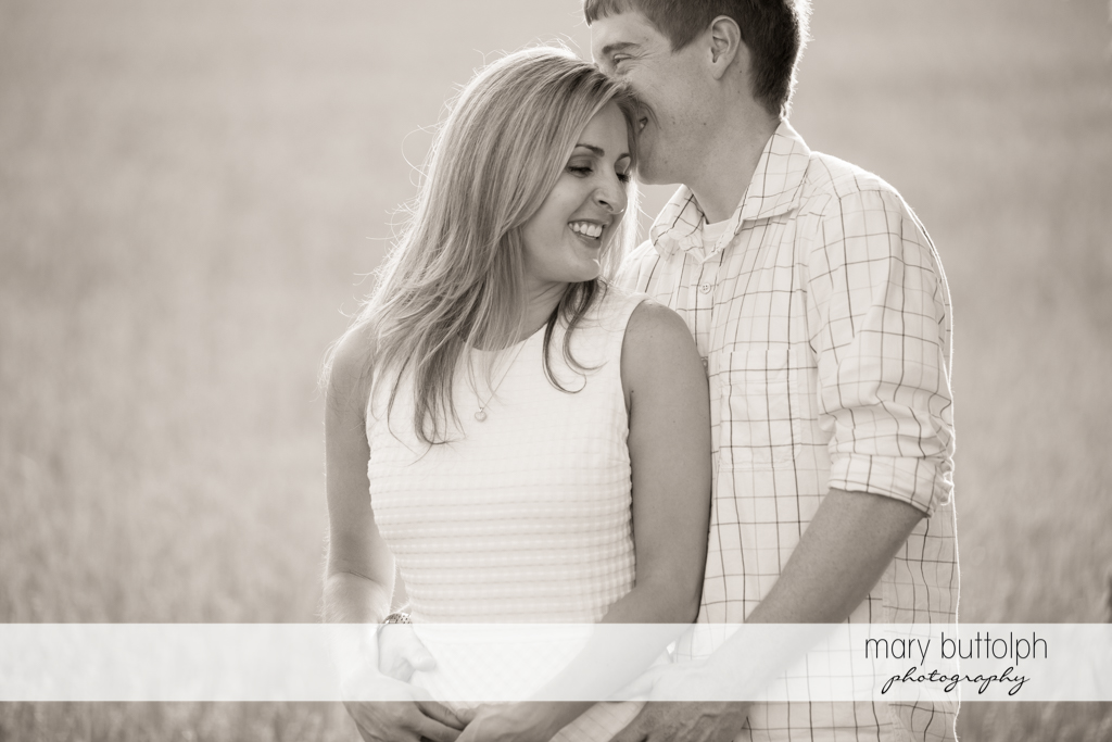 Couple share a tender moment in a wheat field at Skaneateles Engagement